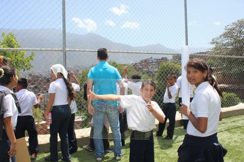 Santiago intenta controlar a unos chamos que saltan emocionados de estar en la cancha, mientras una niña muestra orgullosa el resultado del trabajo en el MANOSHOP.